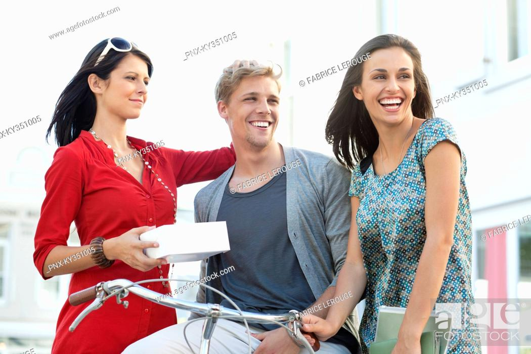 Stock Photo: Smiling young man with two women cycling.