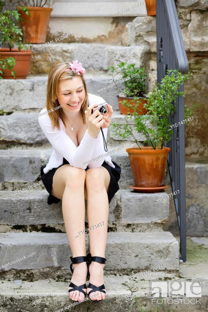Stock Photo: Attractive young woman happy and smiling is watching photos on a small digital photo camera.