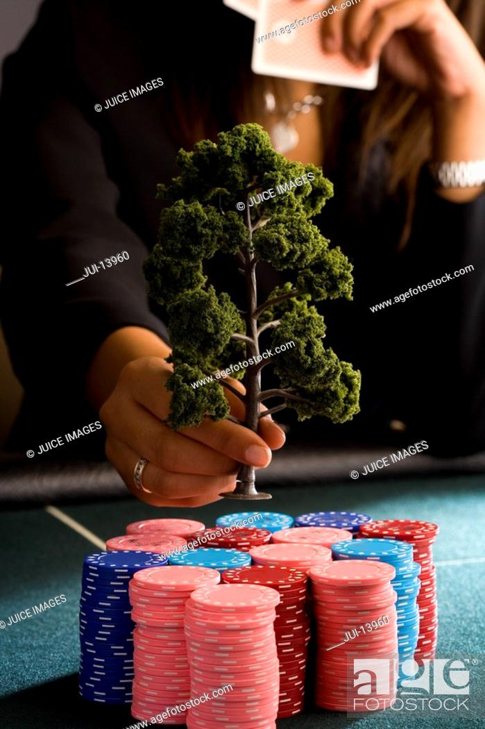 Stock Photo: Woman placing model tree on pile of gambling chips on table, mid section.