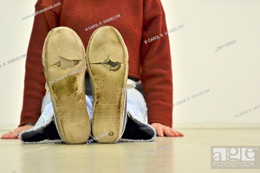 Stock Photo: woman sitting on floor, wearing worn out sneakers.