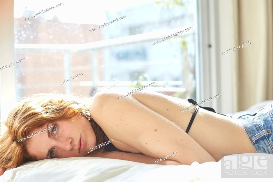 Imagen: Young redhead woman on bed, looking at camera.