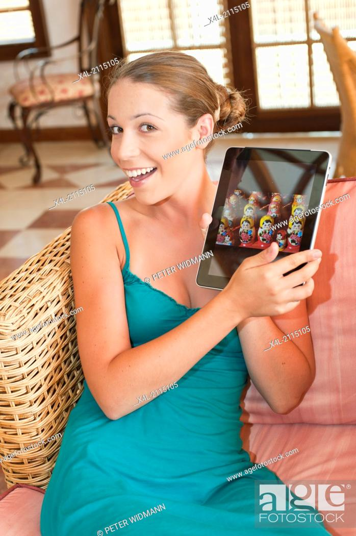 Stock Photo: young, pretty woman on summer holiday, in lobby, with digital tablet, surfing the net (model-released).