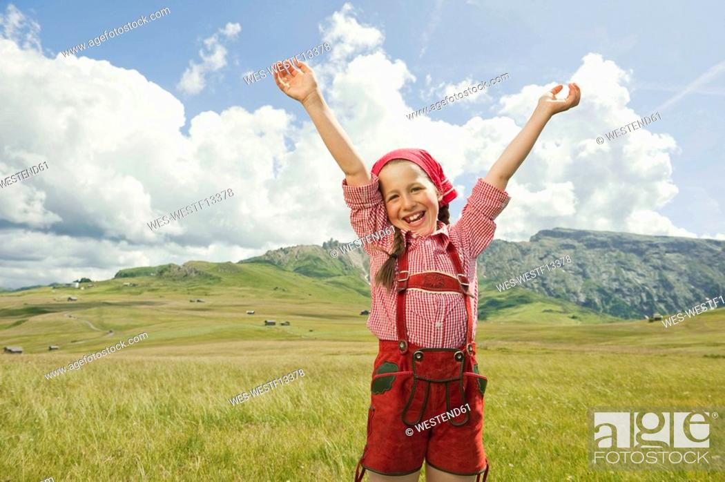 Stock Photo: Italy, Seiseralm, Girl 8-9 in meadow cheering, arms up, portrait.