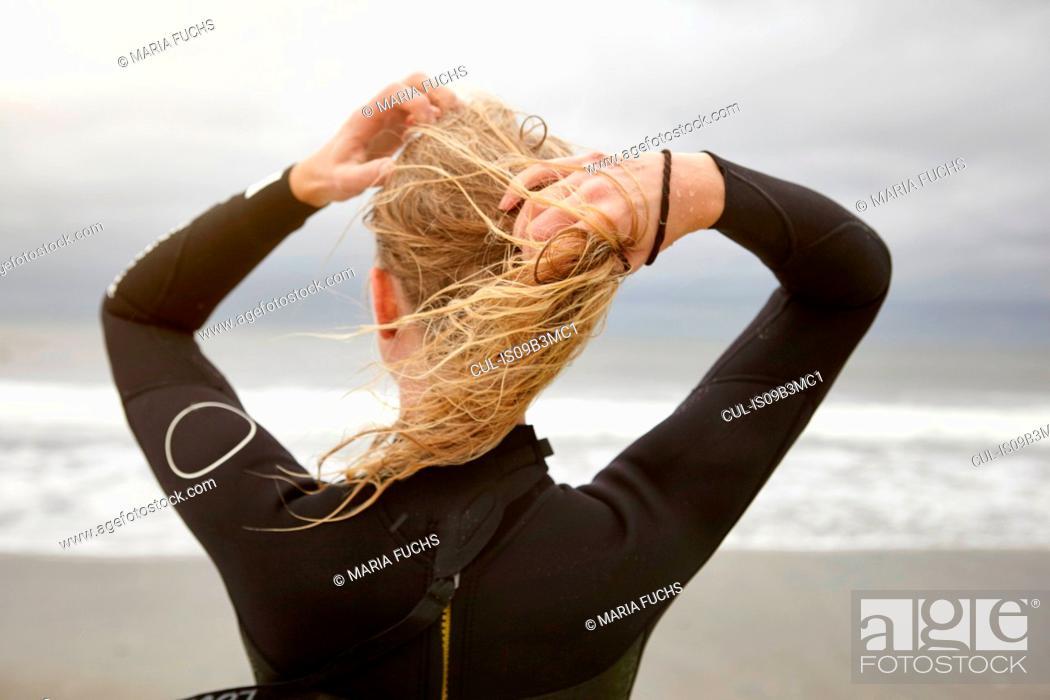 Stock Photo: Rear view of female surfer tying wet blond hair on Rockaway Beach, New York, USA.