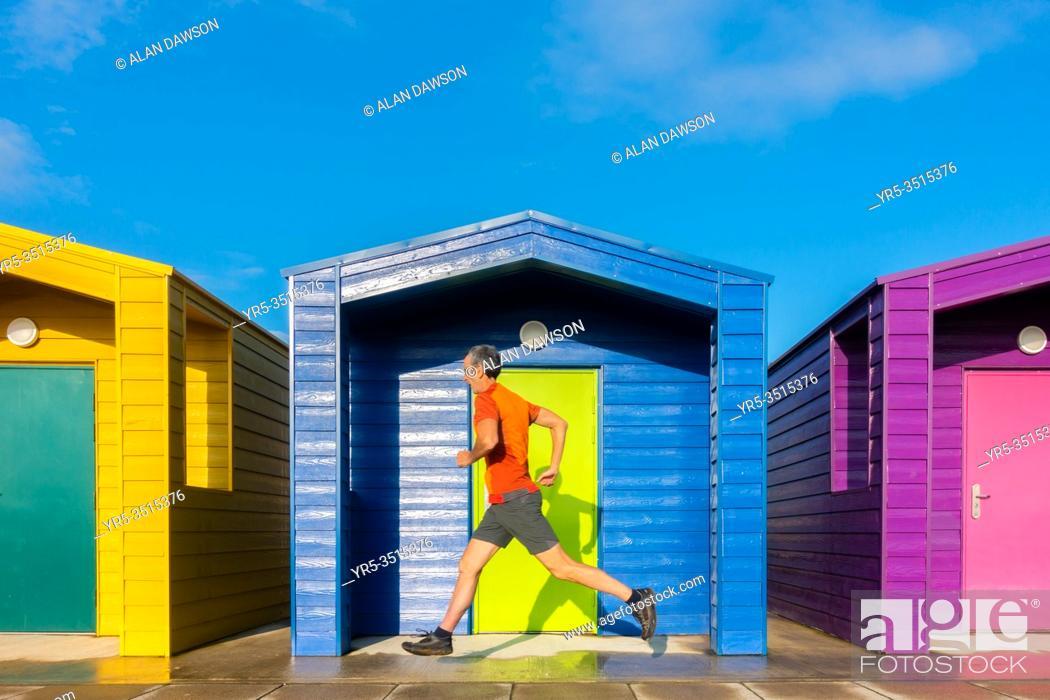 Stock Photo: Mature jogger running past beach huts at Seaton Carew on the north east coast of England. Unite Kingdom.