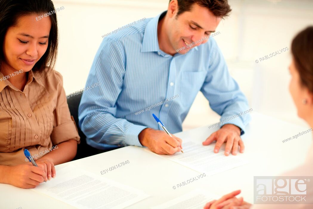 Stock Photo: Portrait of male and female worker signing a contract while smiling and sitting on office desk.
