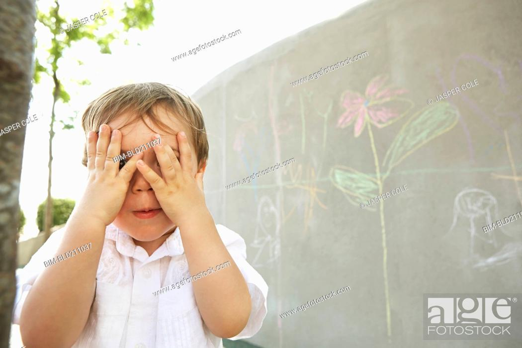 Stock Photo: Mixed race boy covering his eyes outdoors.