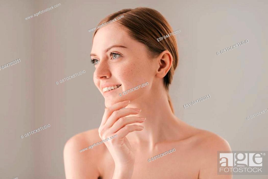 Stock Photo: Glowing with natural beauty. Portrait of attractive young woman with freckles smiling and keeping hand on her chin while standing against grey background.