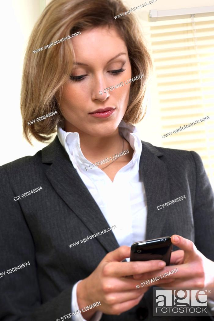 Stock Photo: Businesswoman text messaging on mobile phone.
