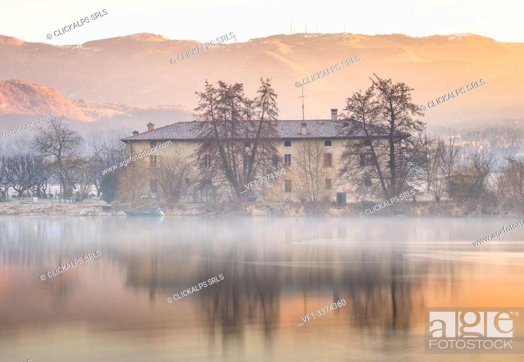 Imagen: Sunrise on a farmhouse reflected on Adda river, Brivio, Lecco province, Lombardy, Italy, Europe.