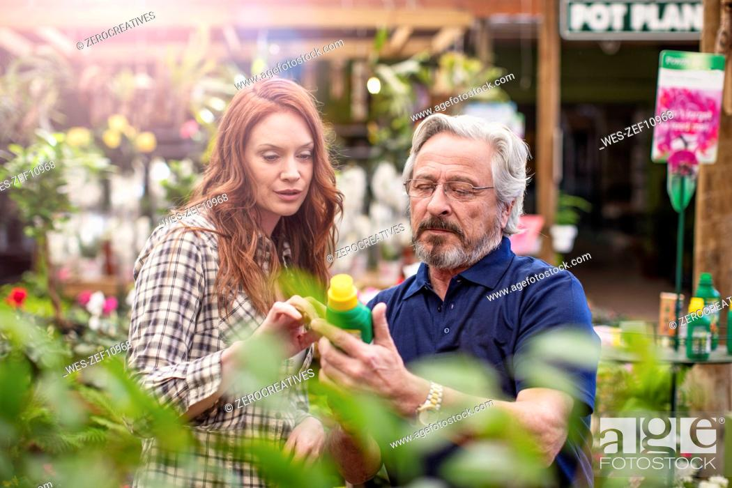 Stock Photo: Gardener helping woman at garden centre.