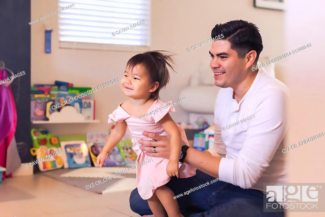 Stock Photo: Baby sitting on the floor in play room holding baby daughter.