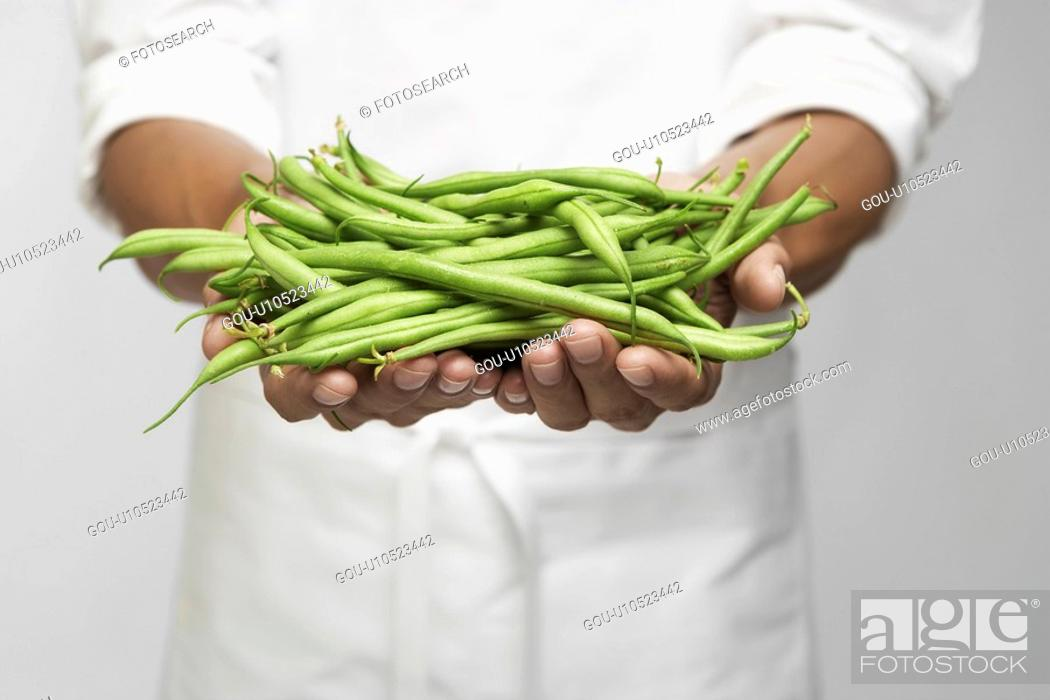 Stock Photo: Green beans on chef's hand (mid section).