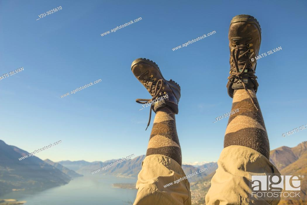 Stock Photo: Hiking Shoes and Legs Up in the Air Over Alpine Mountain Range and Lake maggiore in Ticino, Switzerland.