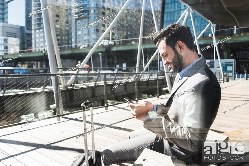 Stock Photo: USA, New York, businessman using cell phone.