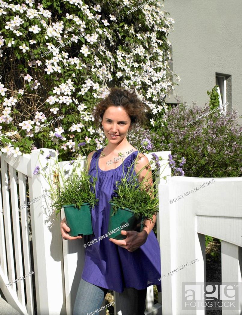 Stock Photo: Woman holding flowerpots.