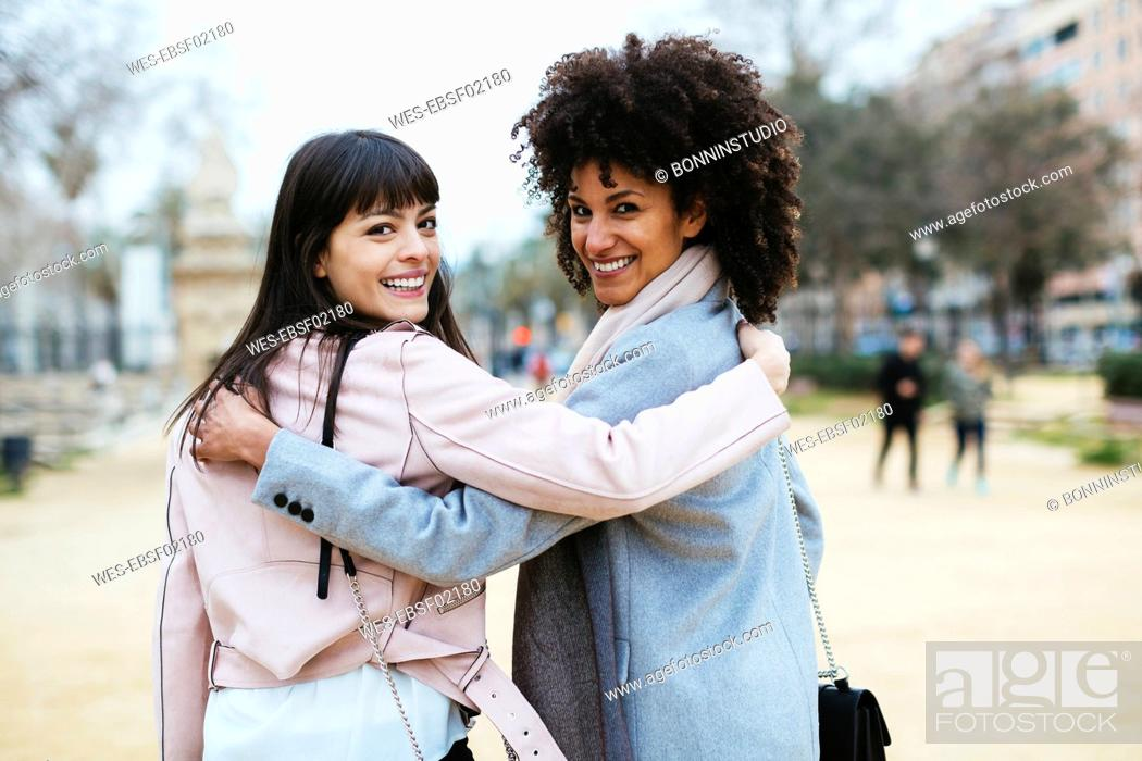 Stock Photo: Spain, Barcelona, portrait of two happy women in city park embracing turning round.