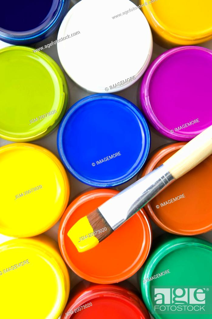 Stock Photo: Jars of color paints and a paintbrush.