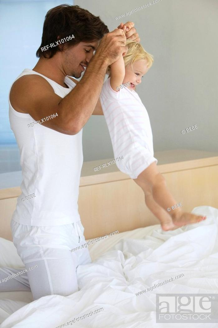 Stock Photo: Young father playing with baby 12-24 months in bed, holing up baby, smiling.