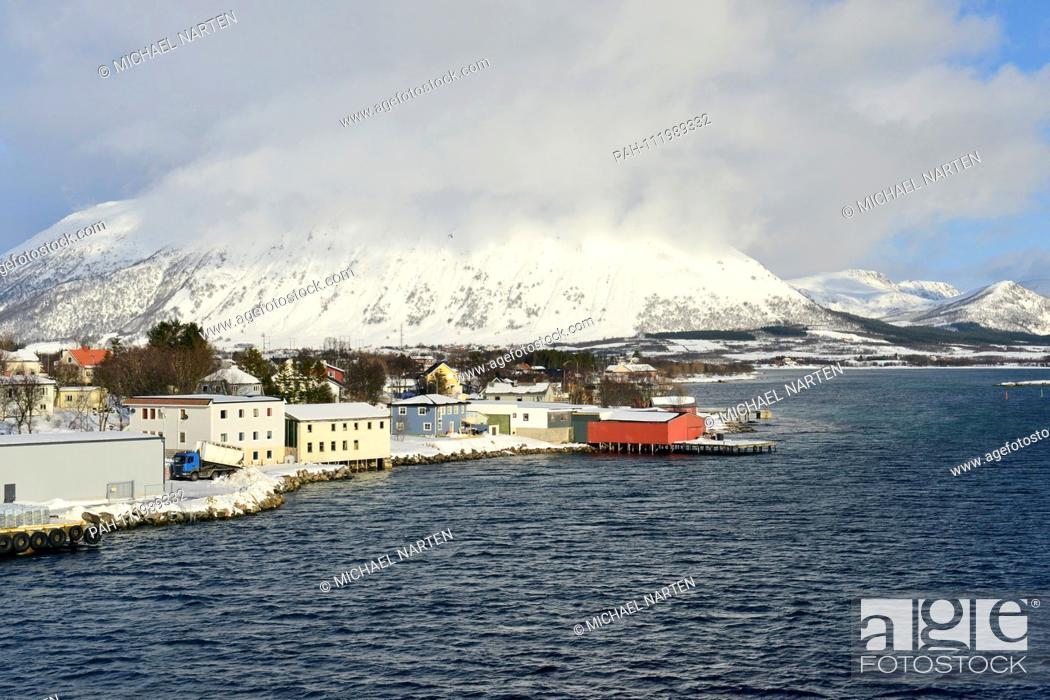 Stock Photo: Houses and buildings from the small village Risøyhamn with a mighty snow-white overcast mountain on the island Andøya, 10 March 2017   usage worldwide.