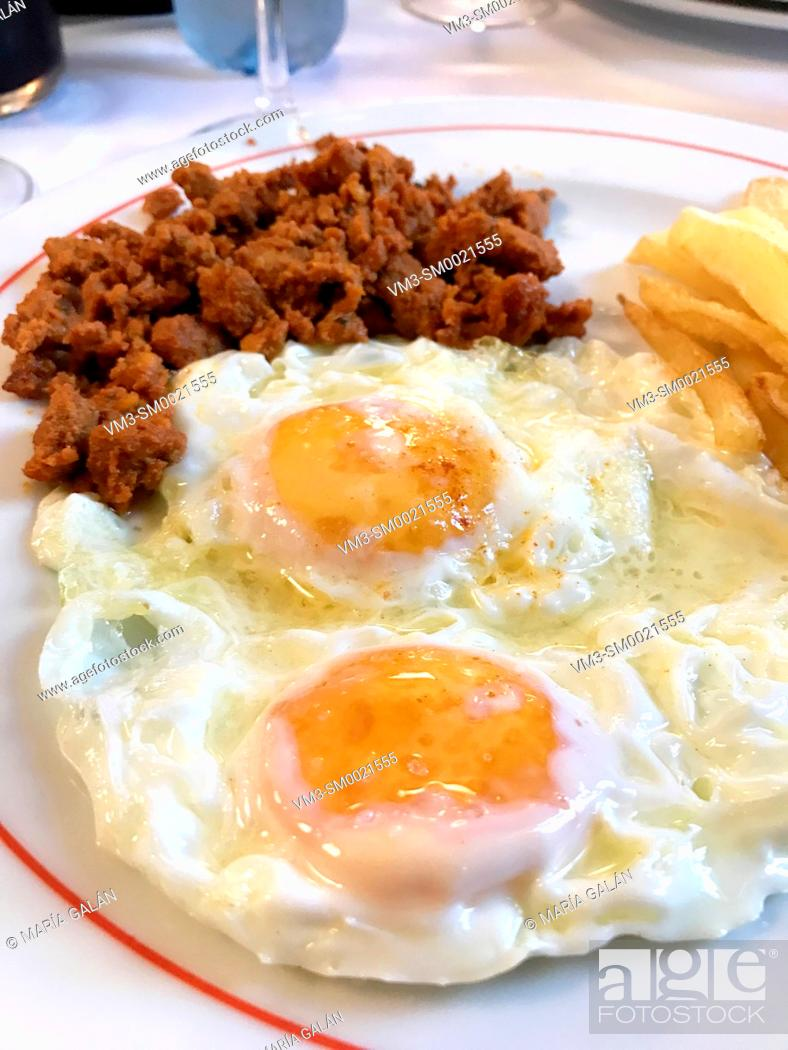 Stock Photo: Two fried eggs with picadillo and chips. Spain.