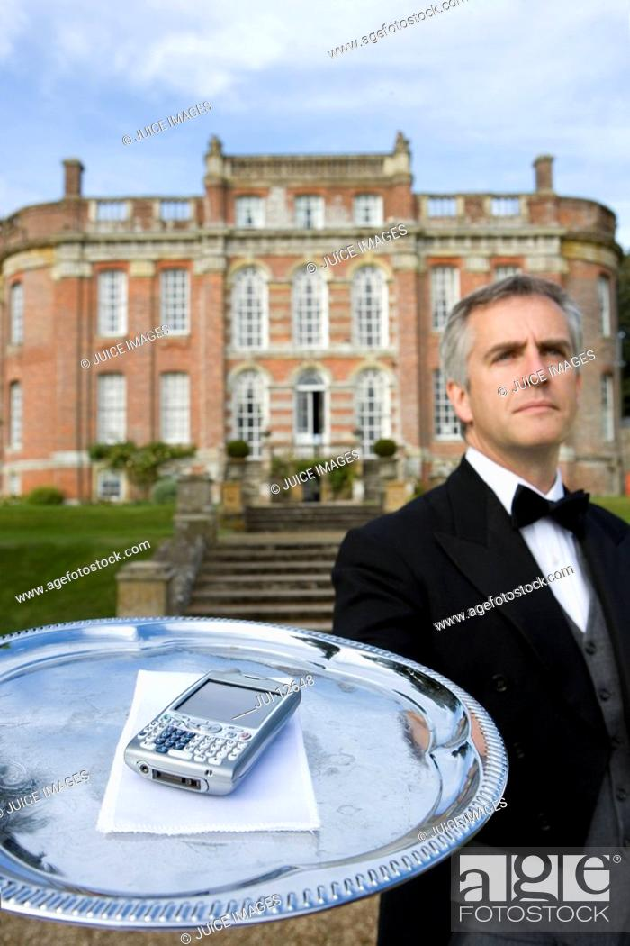 Stock Photo: Mature butler with mobile phone on tray by manor house, low angle view.