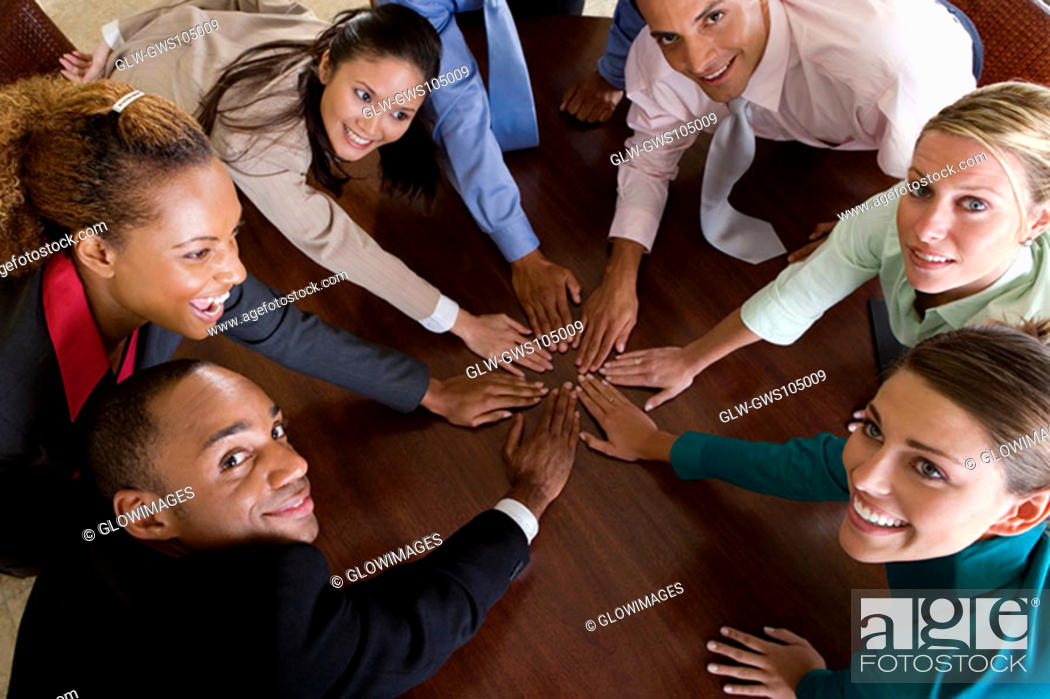 Stock Photo: High angle view of a group of business executives with their hands on a table.