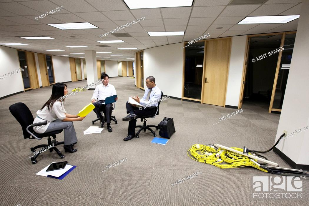 Stock Photo: A mixed race group of three business people sitting in an open space and making plans for a new office layout.