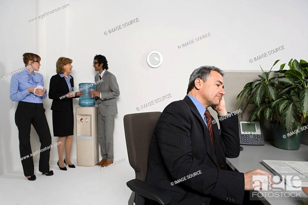 Stock Photo: Businessman at desk with others gossiping by water cooler.