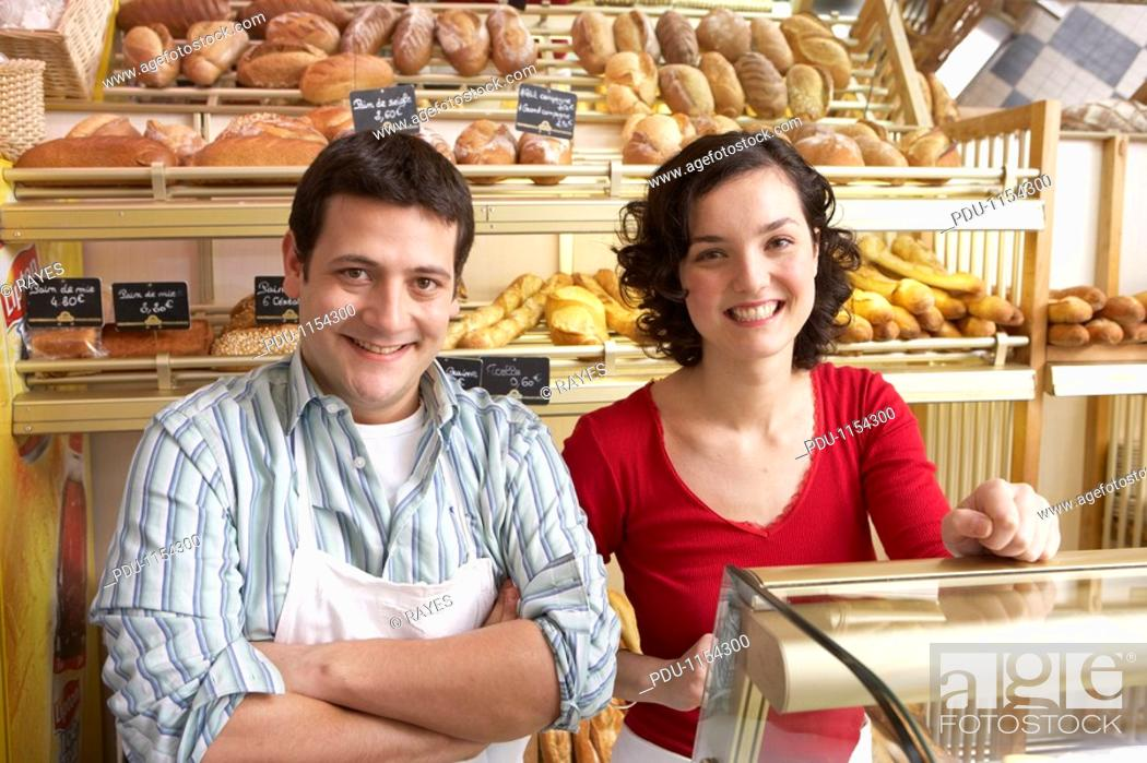 Stock Photo: Young man and woman in bakery, smiling, portrait.