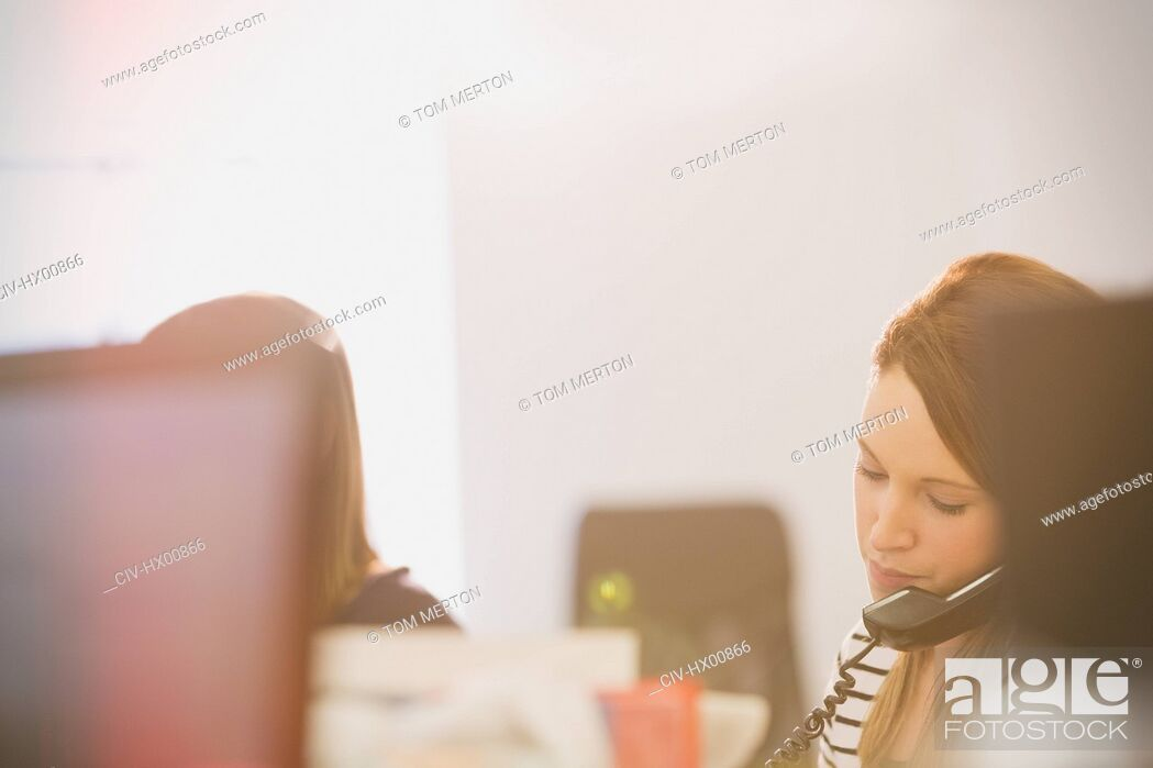 Stock Photo: Businesswoman talking on telephone in office.