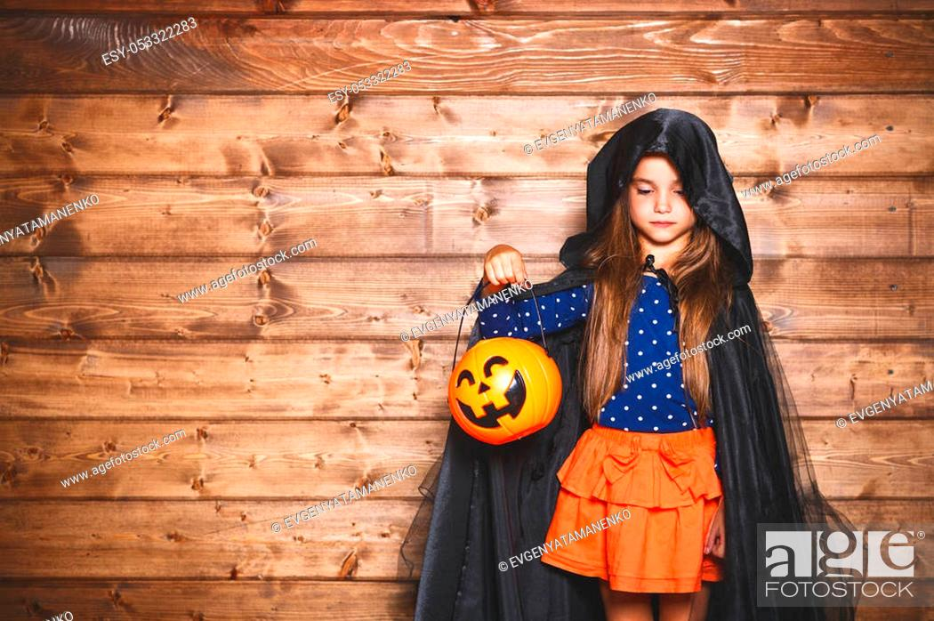 Stock Photo: Laughing funny child girl in a witch costume in halloween.
