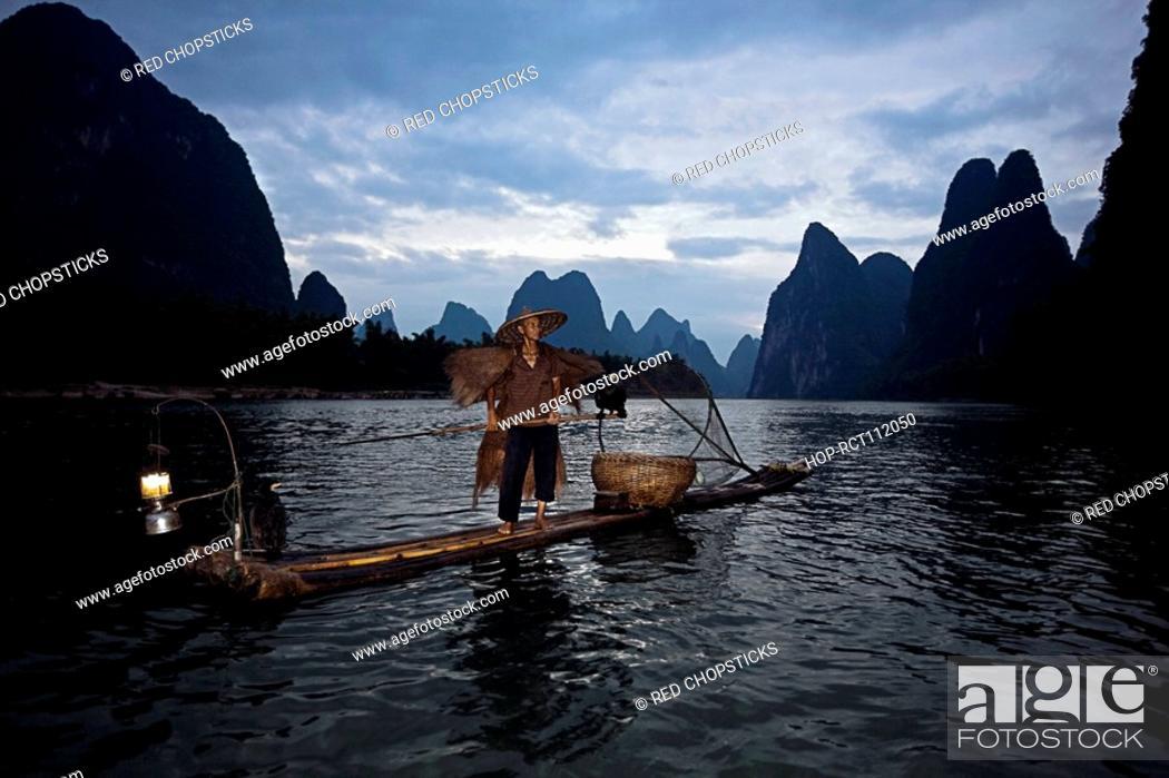 Stock Photo: Fisherman standing on a wooden raft in a river, Li River, XingPing, Yangshuo, Guangxi Province, China.