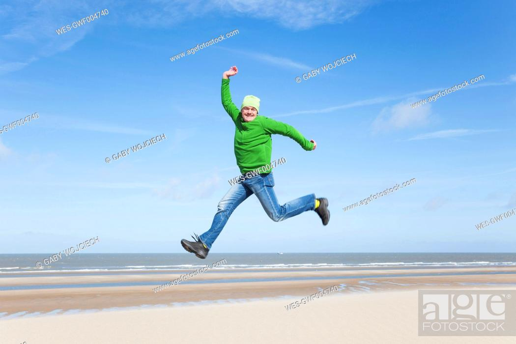 Photo de stock: Enthusiastic mature man jumping on beach.