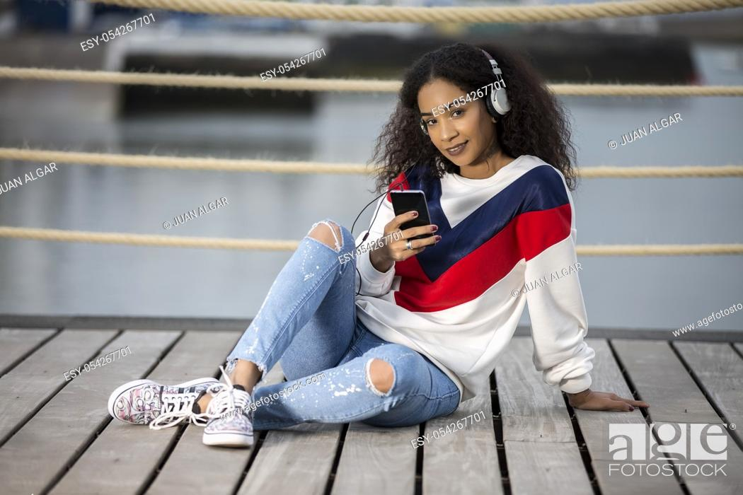 Stock Photo: Pretty ethnic girl in stylish casual outfit using headphones with phone and looking flirty at camera.