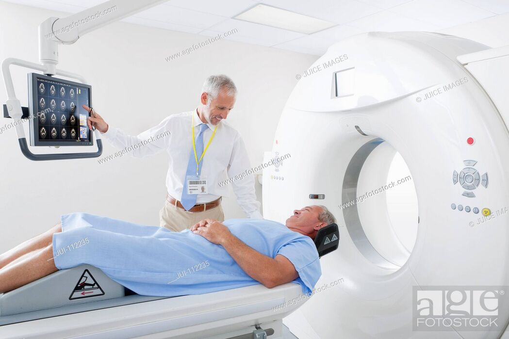 Imagen: Doctor reviewing CT scan digital brain scan with patient in hospital.