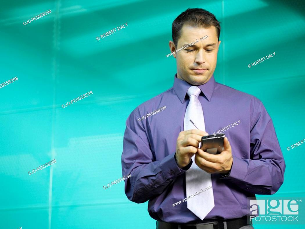 Stock Photo: Businessman using PDA in blue office.