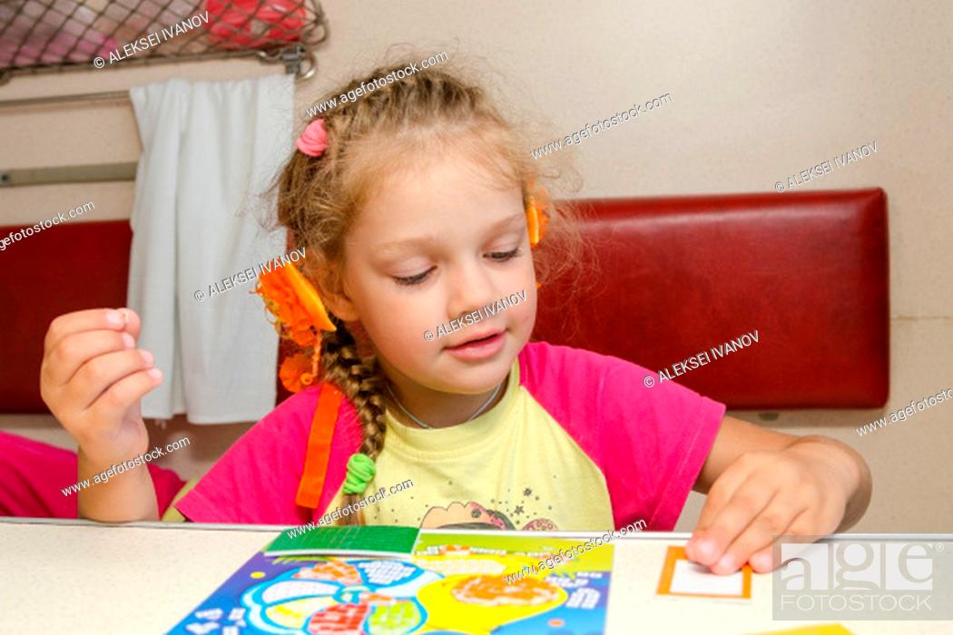 Stock Photo: Little girl on the train sits at a table on the lower second-class place car and enthusiastically skin application.