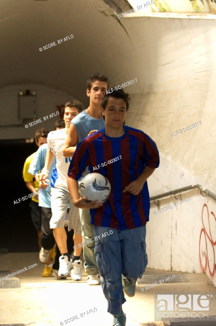 Stock Photo: Street soccer team emerging from tunnel.