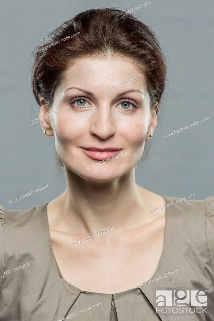 Stock Photo: Portrait of smiling mid adult woman against gray background.