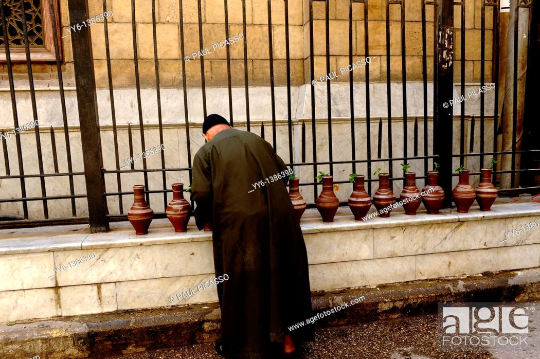 Stock Photo: imam filling up water bottles, outside the Al-Hussein Mosque , which sits on the site of the cemetery of the Fatimid caliphs , islamic cairo, cairo, egypt.