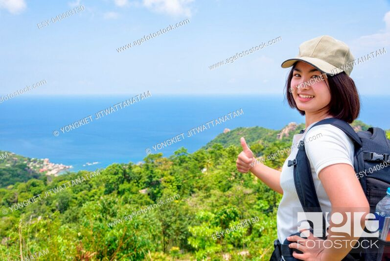 Imagen: Women tourist with a backpack wear cap raise thumbs up for the beautiful nature landscape blue sea and sky from high scenic viewpoint at Koh Tao, Surat Thani.