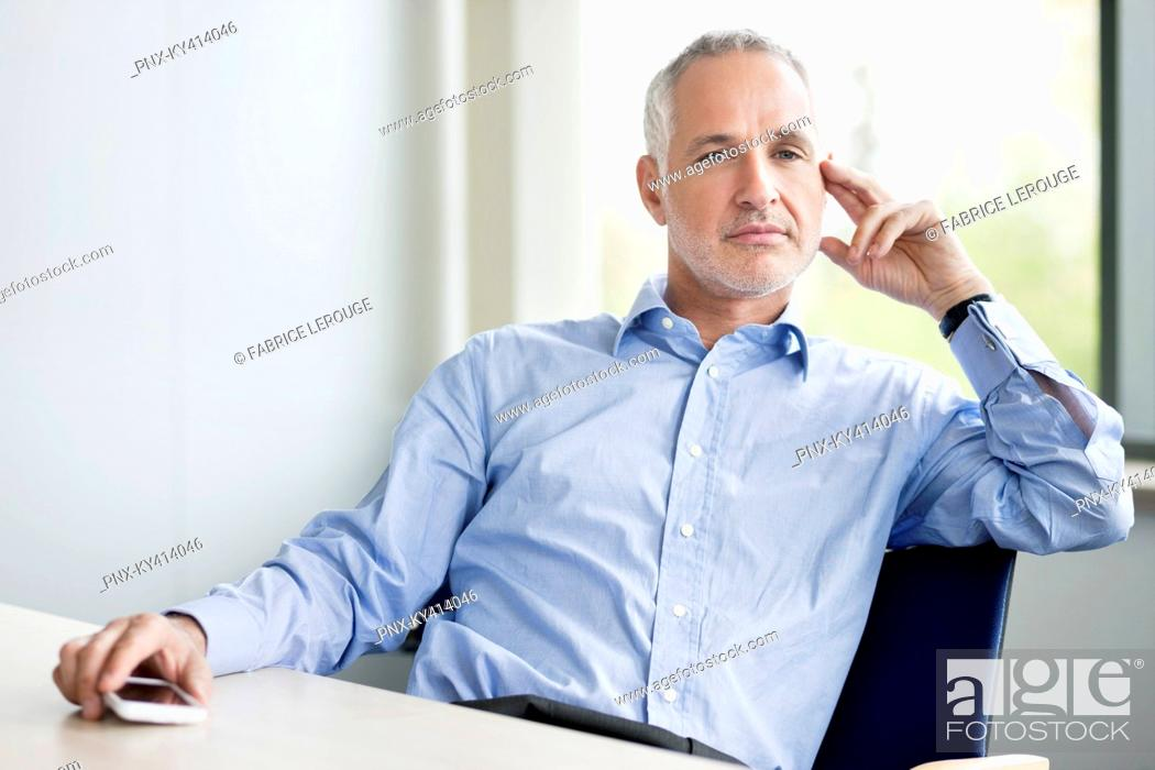 Stock Photo: Businessman sitting in an office.