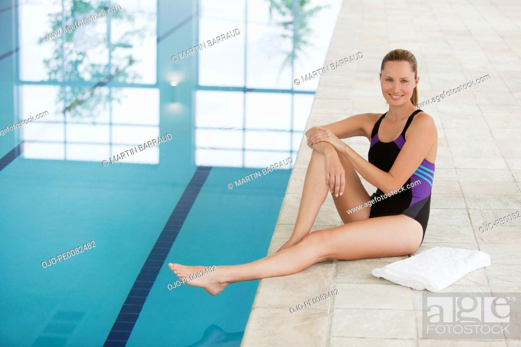Stock Photo: Portrait of smiling young woman sitting at edge of swimming pool.