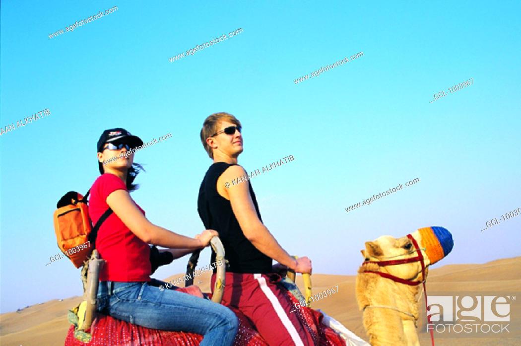Stock Photo: Tourists riding a camel in the desert near Hatta, United Arab Emirates.