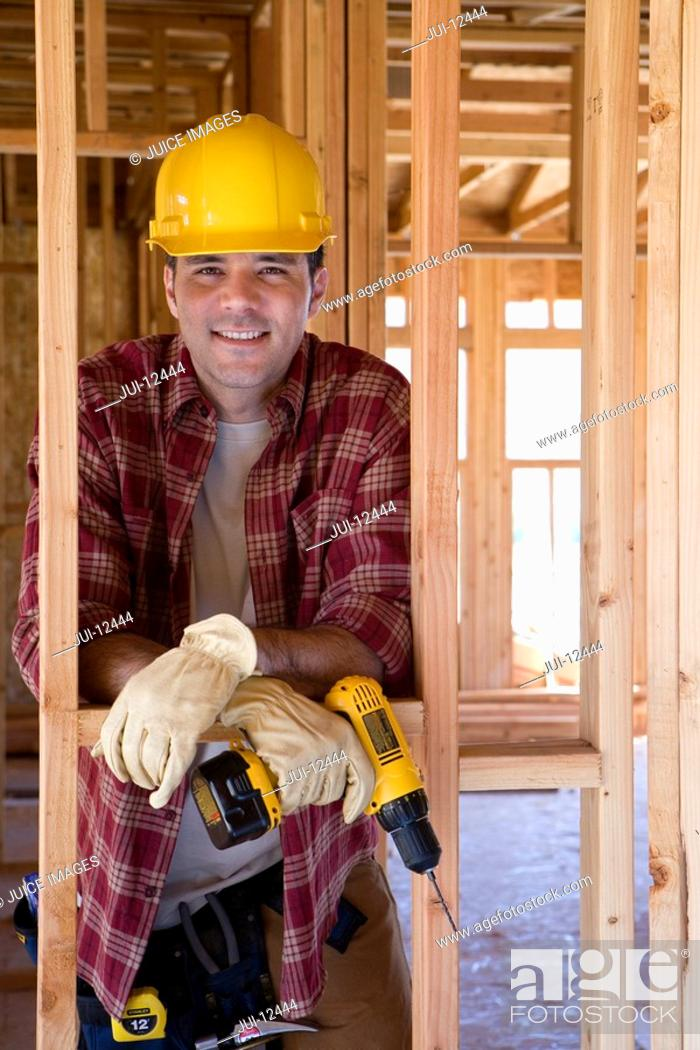 Stock Photo: Builder in hardhat with drill in partially built house, portrait.