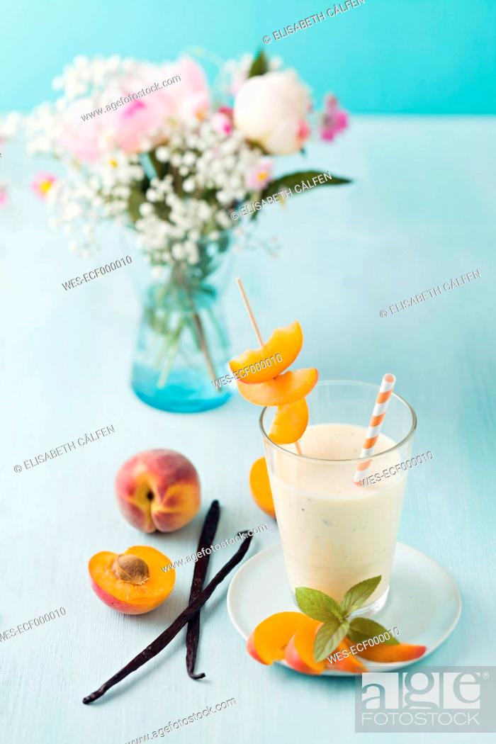 Stock Photo: Vanilla and peach smoothie with flower bouquet on table, close up.