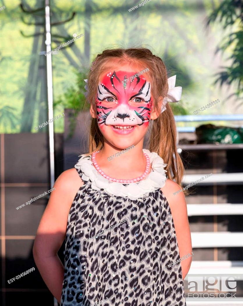 Imagen: Little girl stands with face painted as a cat.