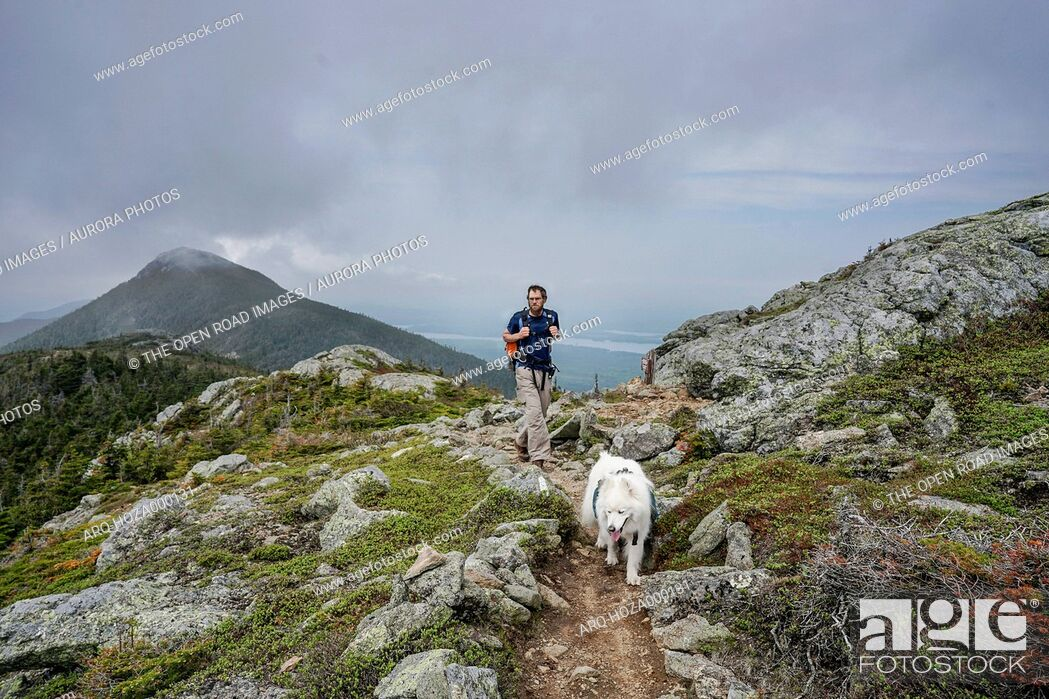 Imagen: Man hikes with dog on Avery Peak above Flagstaff Lake along the Appalachian Trail in Maine's Bigelow Mountains.