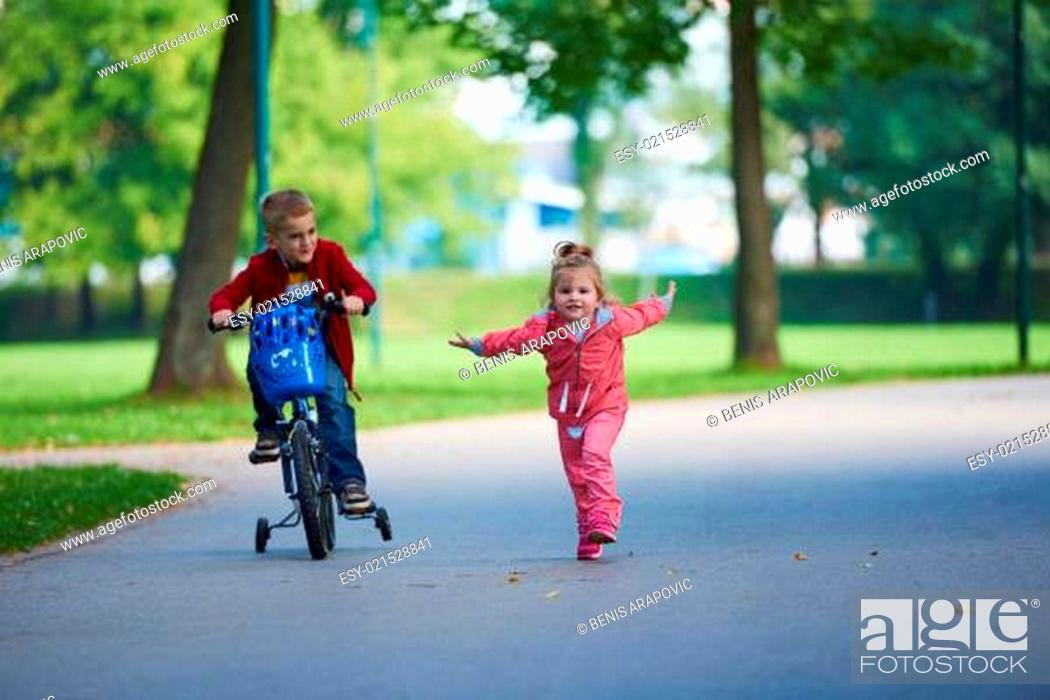 Stock Photo: happy kids in park, boy and girl in nature with bicycle have fun.